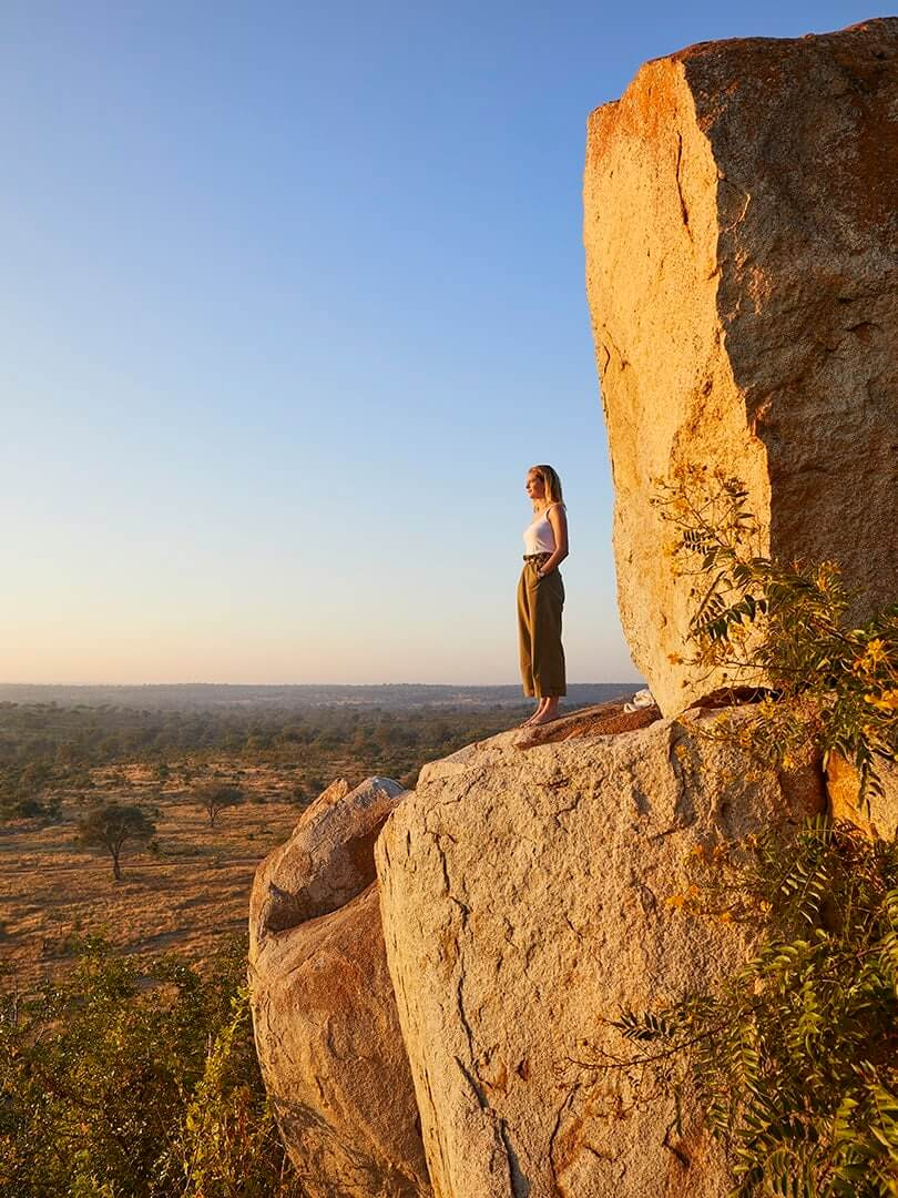 Woman standing on a cliff edge looking out across the plains at Londolozi, South Africa. Photograph by Elsa Young.