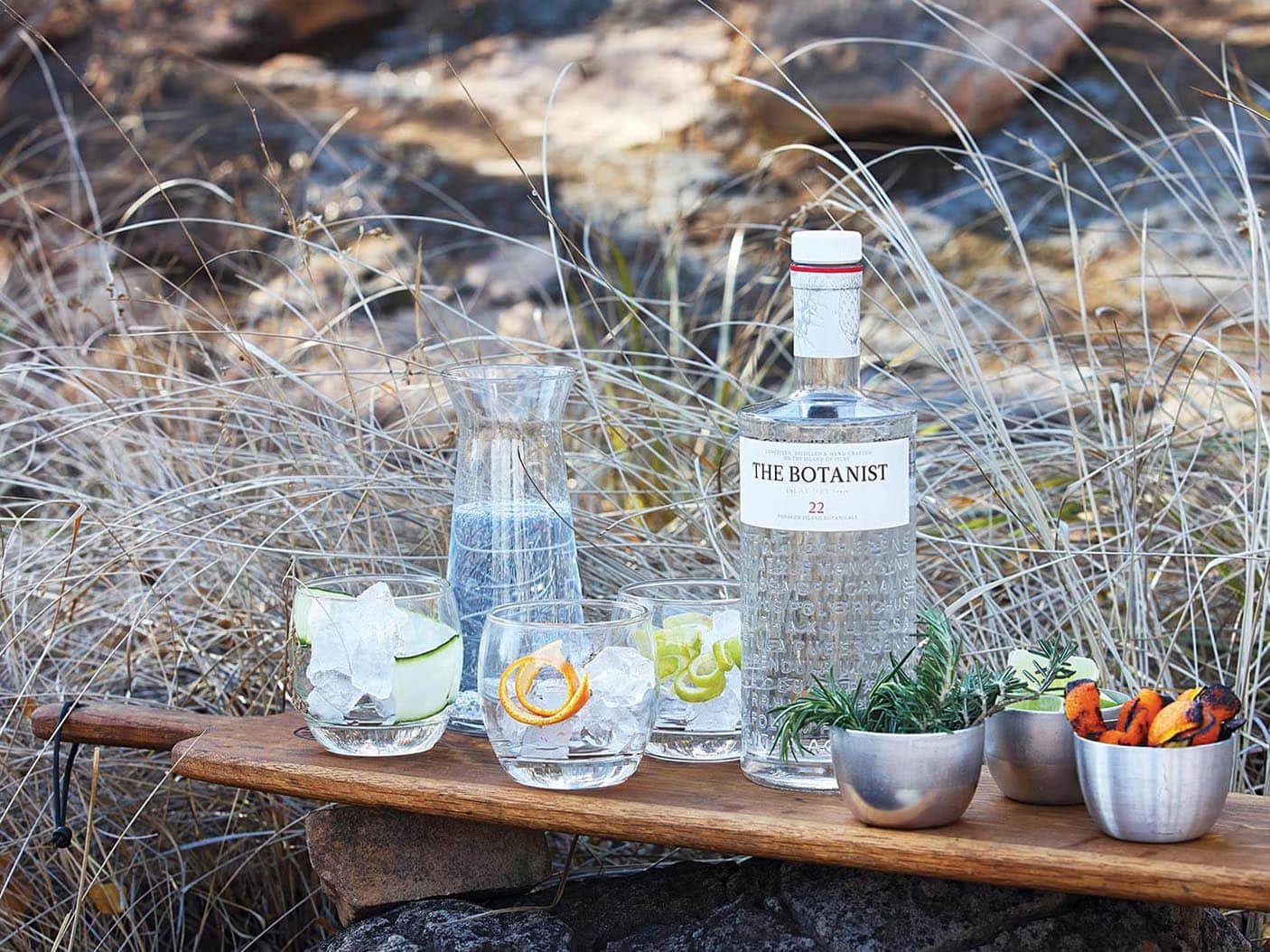 Drinking glasses and a bottle of The Botanist gin outdoors on a serving board. Photo by Elsa Young Photography.