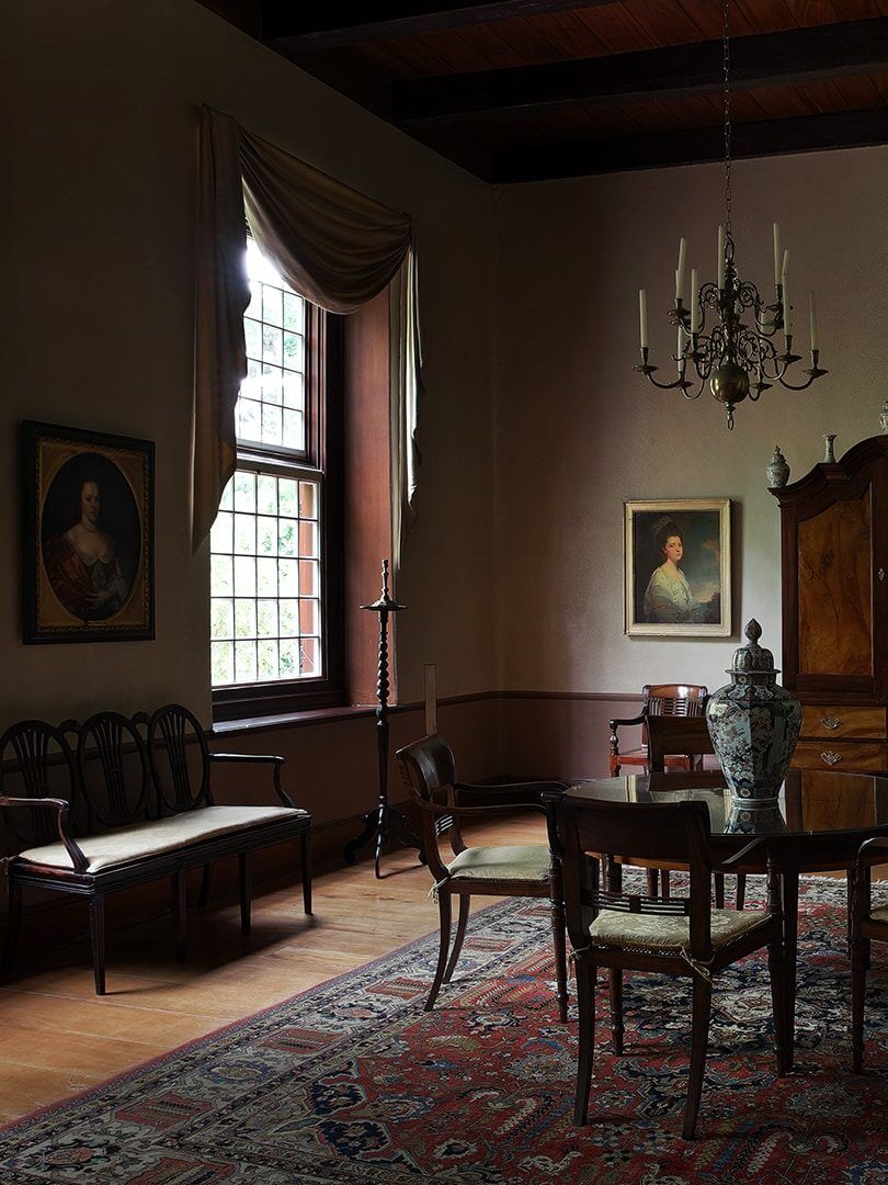 Beautiful, moody interior of a building at Vergelegen Wine Estate with massive sash windows and antiques. Photo by Elsa Young.