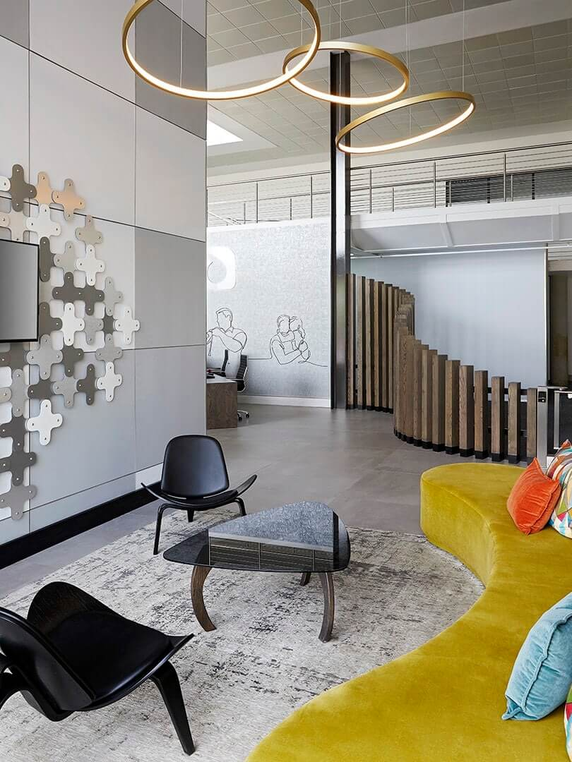 Playful company reception area with a brightly coloured couch and modern chairs. Elsa Young Photography.