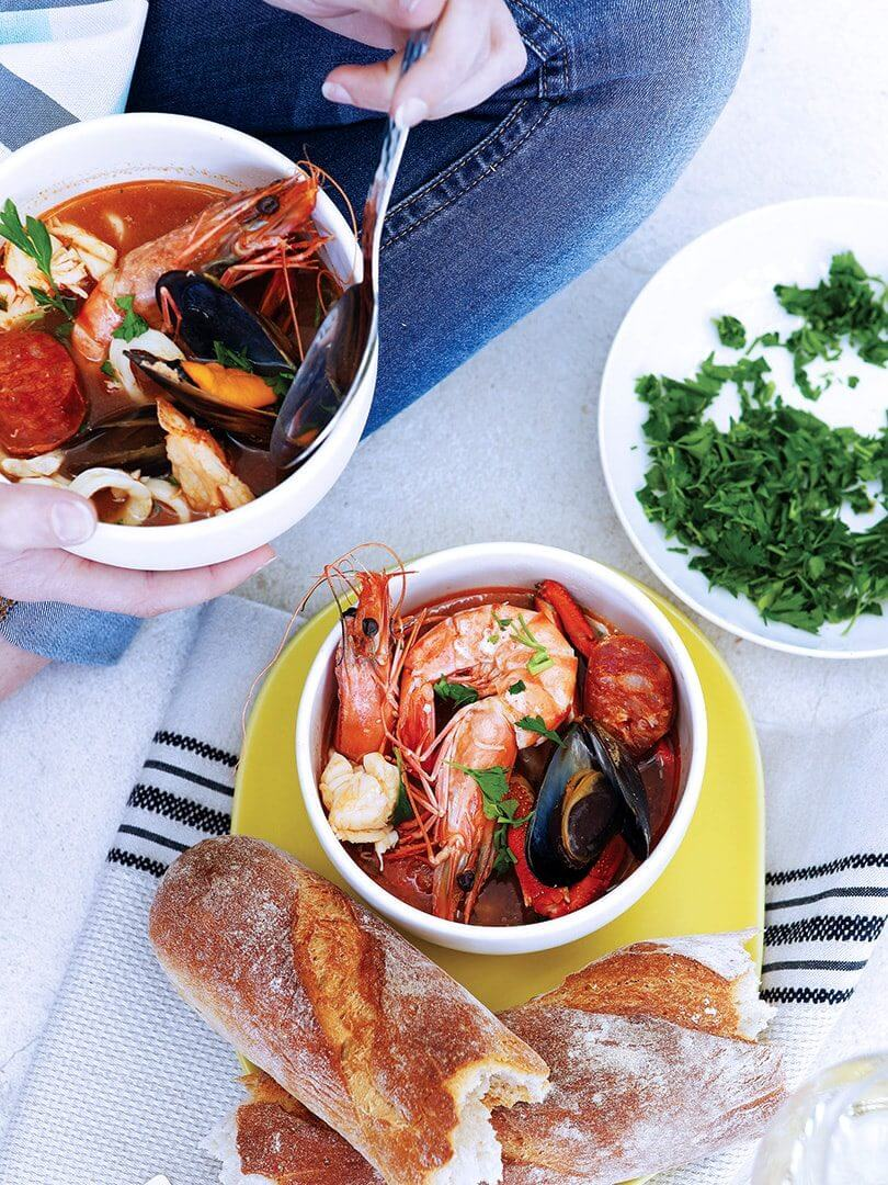 Two bowls of rich seafood bisque with a loaf of French bread. Photograph by Elsa Young.