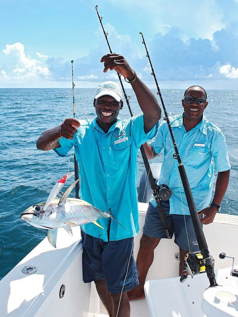 Two men smiling on a boat after having just caught a fish. Photo by Elsa Young.