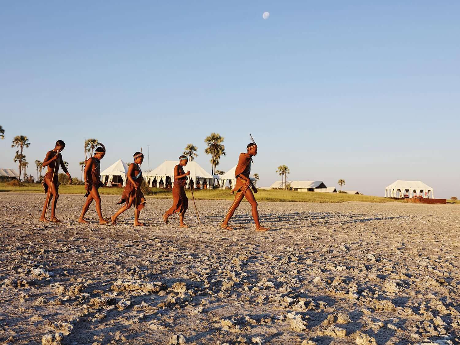 San tribespeople walking across sand in Botswana. Photo by Elsa Young.