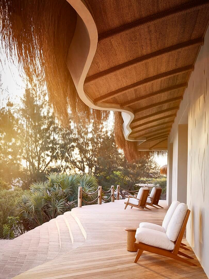 Chairs on a wooden deck under a magnificent hand-crafted grass roof overhang at Kisawa Sanctuary. Mozambique. Photo by Elsa Young.