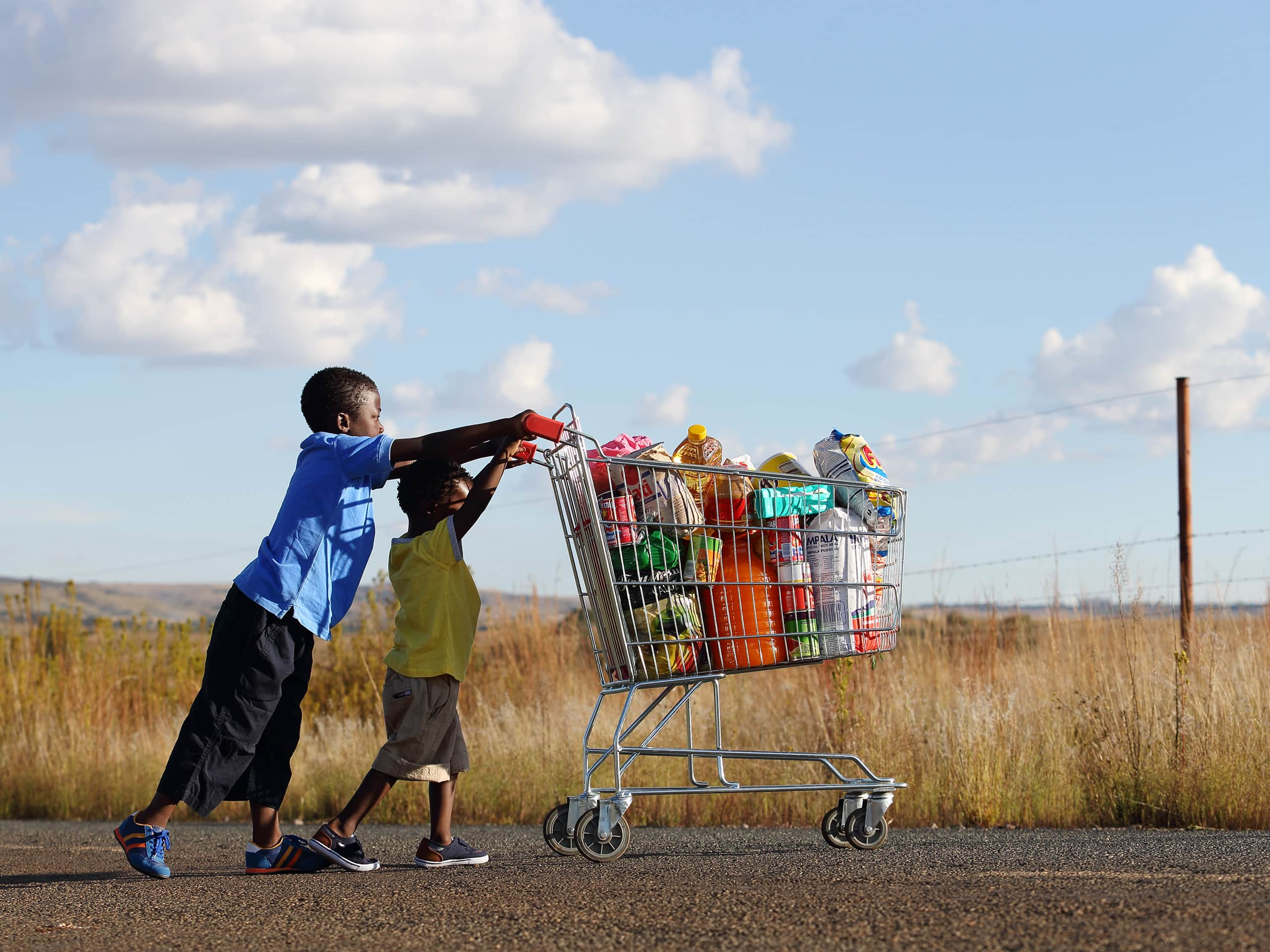 Two small boys pushing a trolley of food along a tarred road. Photograph by Elsa Young.