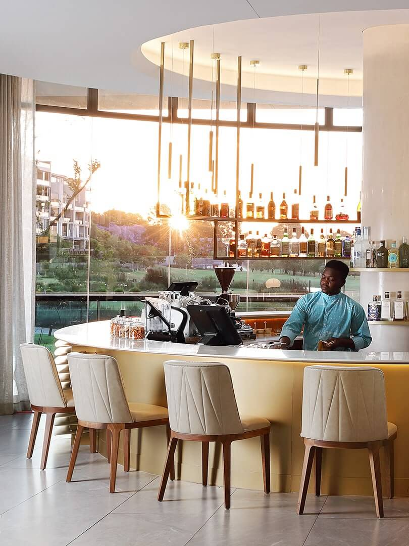 Barman behind his counter cleaning glasses at the elegant Houghton Hotel and Spa. Photograph by Elsa Young.