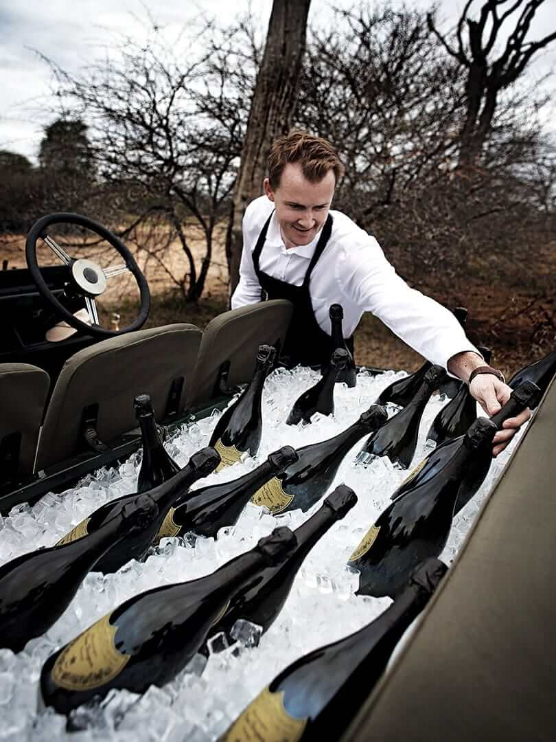Man stacking the back seat of an open land rover with ice and dozens of bottles of Dom Perignon. Photo by Elsa Young.