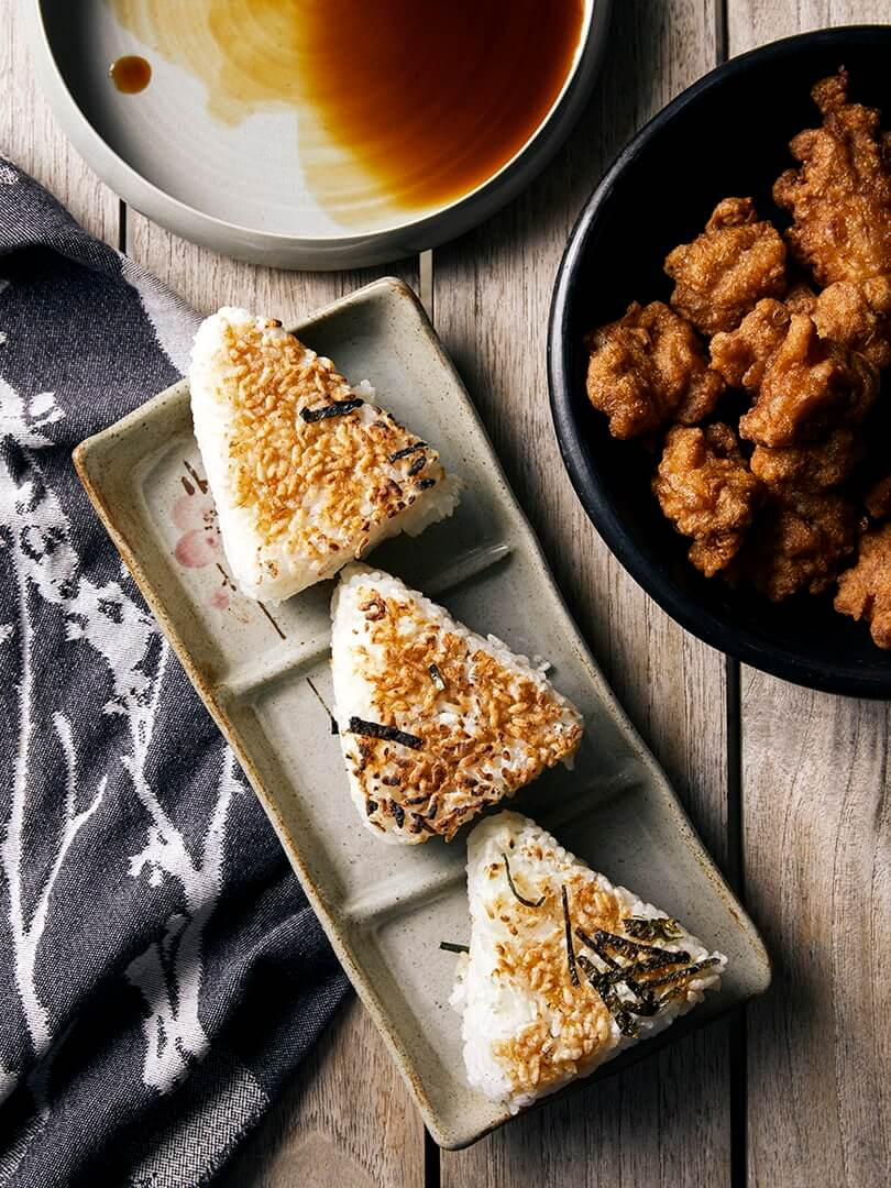 Triangular onigiri on a Japanese plate with dipping sauce. Photograph by Elsa Young.