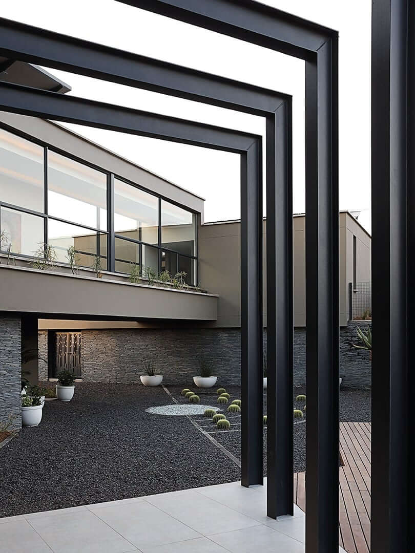 Modern house with cantilevered external black beams, photograph by Elsa Young