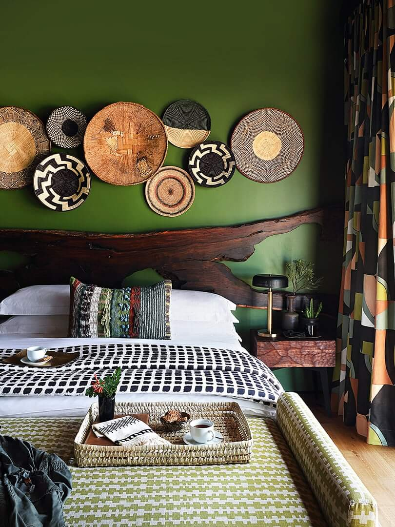 Eclectic bedroom with African bed throws and woven baskets on the walls at Toulon House in South Africa. Photo by Elsa Young.