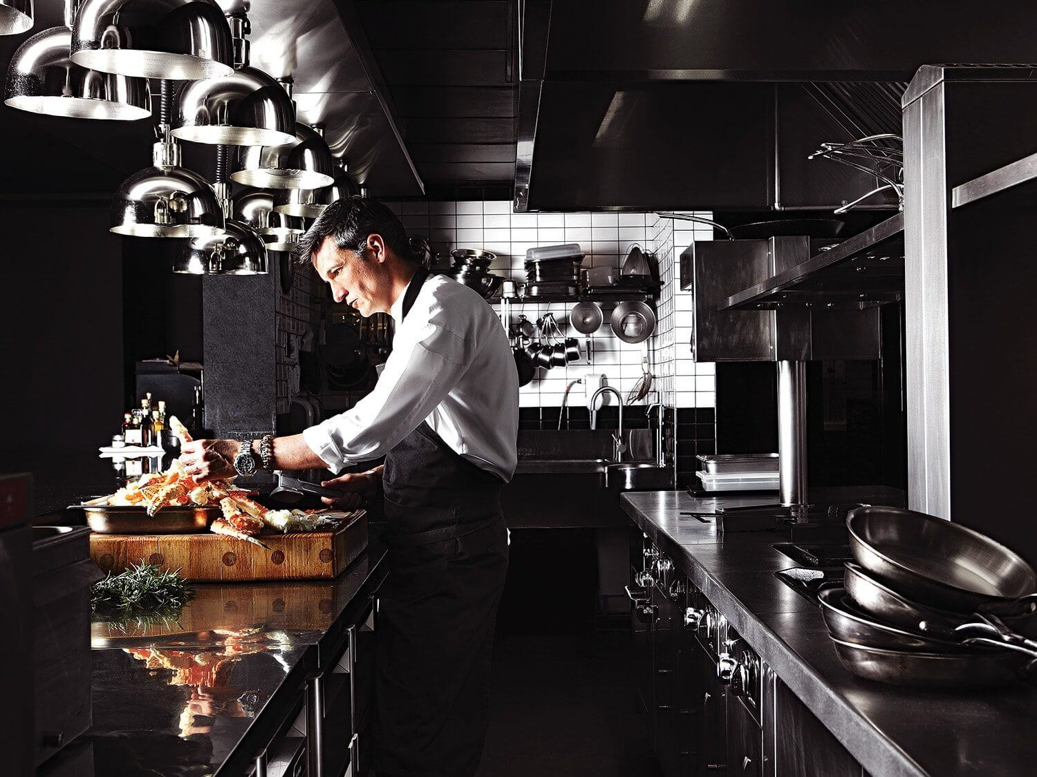 Chef David Higgs preparing food in the kitchen of his restaurant, Marble. Photo by Elsa Young.