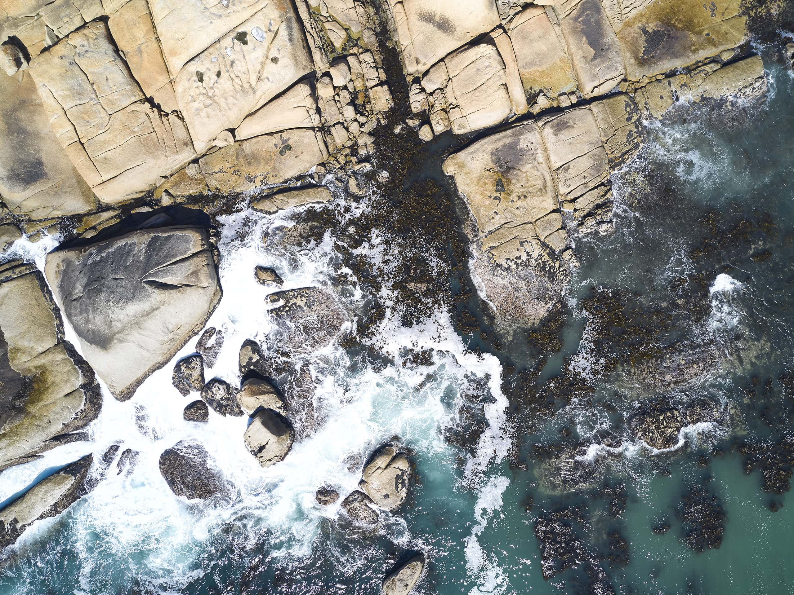 Evocative drone photograph of waves crashing into rocks in the Western Cape, South Africa. Photograph by Elsa Young.