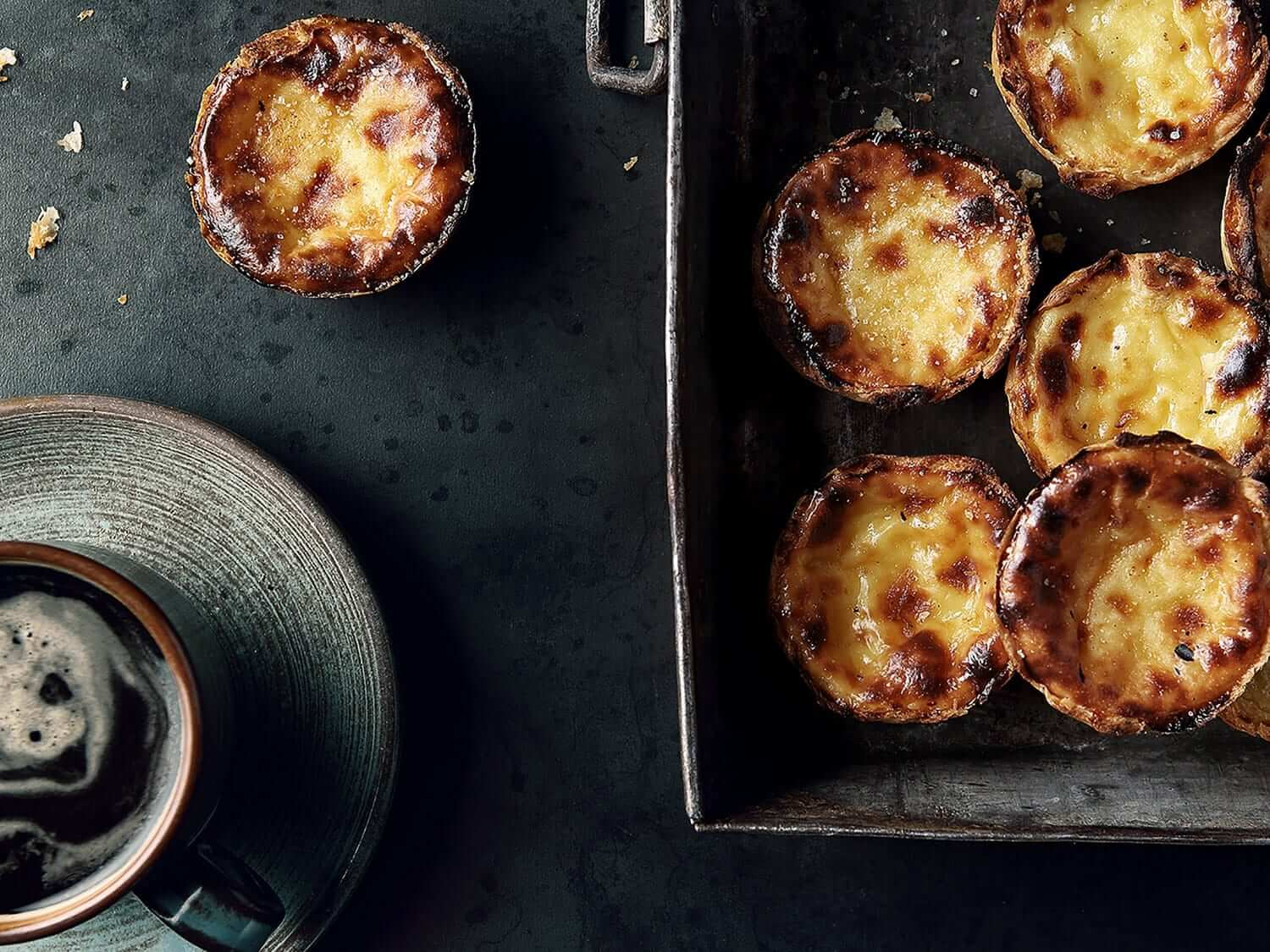 Mouth-watering Pastéis de Nata and a cup of coffee seen from above. Photo by Elsa Young.