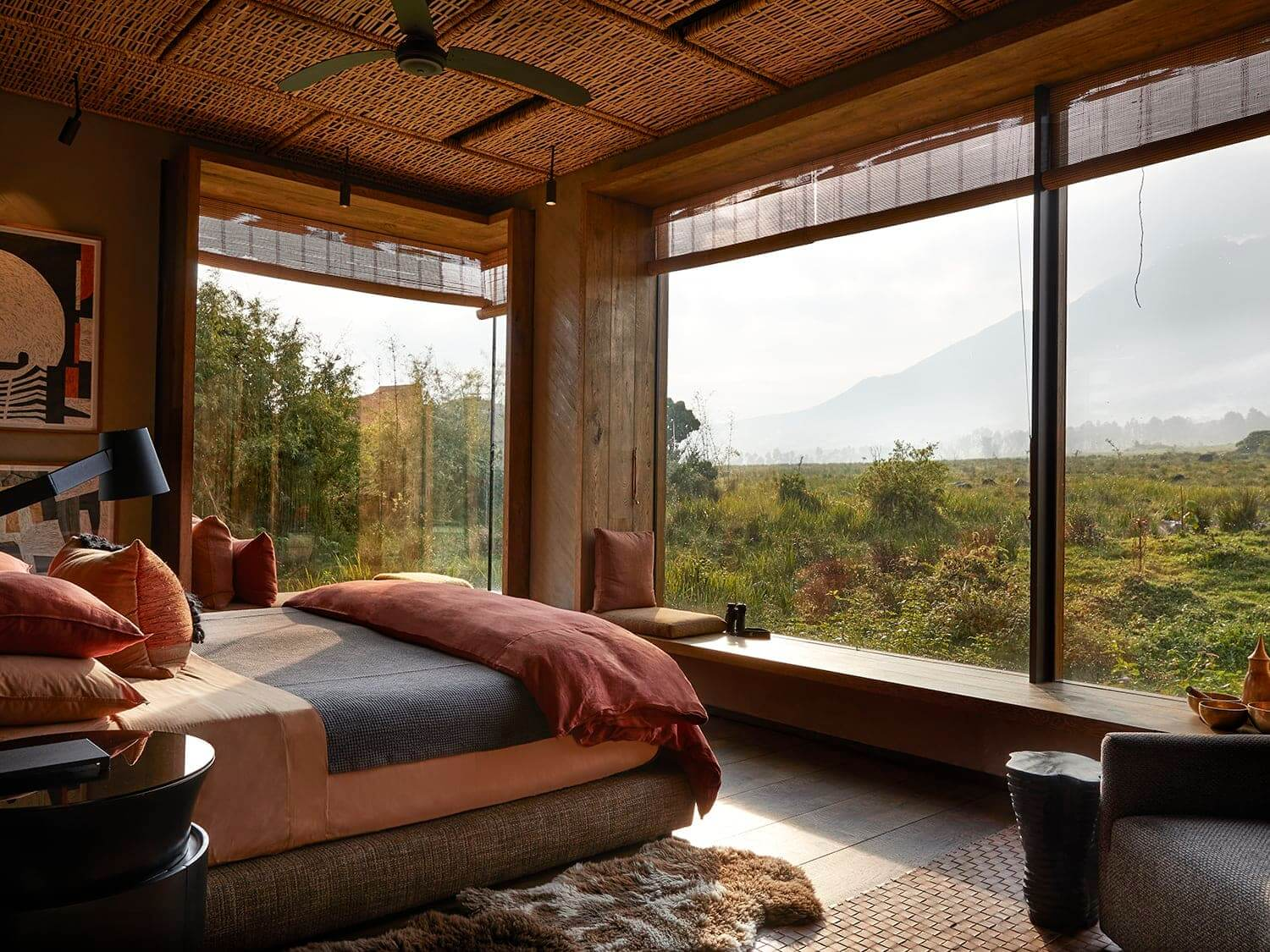 Beautiful bedroom with woven ceilings and huge plate glass windows overlooking a distant volcano at Singita Kwitonda, Rwanda. Photo by Elsa Young Photography.